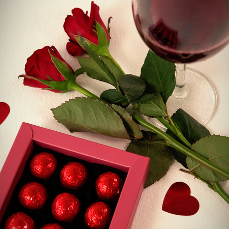 Wine, roses and chocolates with red hearts around