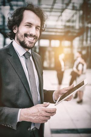 Portrait of businessman holding digital tablet in office premises