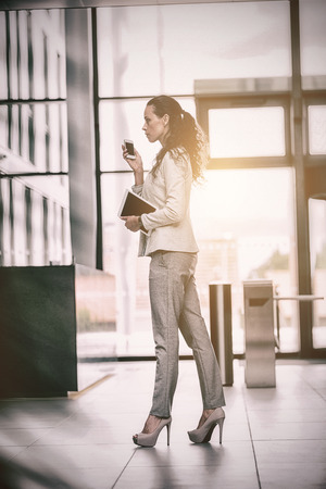Businesswoman holding digital tablet and mobile phone walking in office lobby Stock Photo