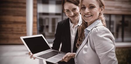 Portrait of businesswomen using laptop and digital tablet in office premises