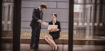 premises: Businessman showing digital tablet to colleague in office premises Stock Photo
