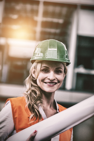 Portrait of architect woman in hardhat holding blueprints in office