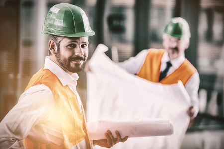Portrait of architect in hard hat standing with blueprint in office corridor Stock Photo