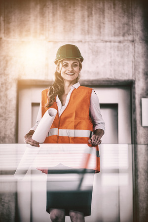 Portrait of architect woman in hardhat holding blueprints in corridor at office Stock Photo