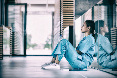 Boczny widok pielęgniarki obsiadanie na podłoga w szpitalnym korytarzu