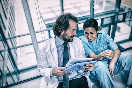 Glücklicher Doktor, der mit Krankenschwester über Bericht im Krankenhaus sich bespricht