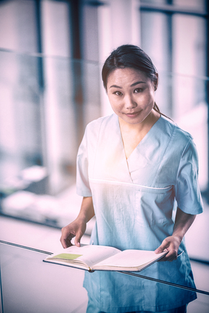 uneasy: Portrait of a nurse holding a diary in hospital
