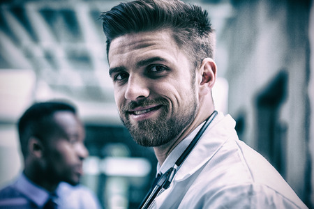 Portrait of smiling doctor standing in hospital Stock Photo