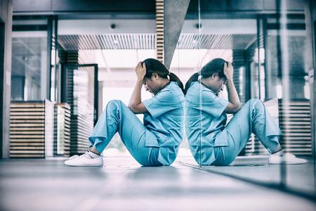 Stressed nurse sitting in hospital corridor Stock Photo - 71083397