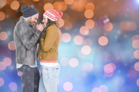 Young couple in warm cloth standing face to face and shivering against glowing background Stock Photo