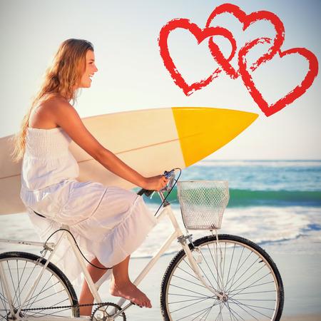 beautiful surfer in sundress on bike holding surfboard at beach