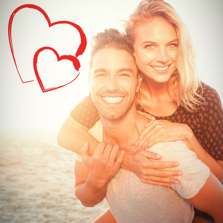 portrait of a young man piggybacking beautiful woman Portrait of  young man piggybacking beautiful woman at beach on sunny day Stock Photo