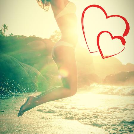 beautiful jumping blond in white bikini at beach