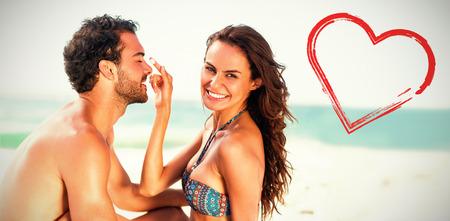 Print against happy girlfriend putting sunscreen on boyfriends nose