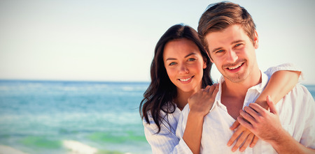 Cheerful couple embracing and posing on the beach on a sunny day