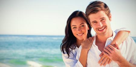 Vrolijk paar omarmen en poseren op het strand op een zonnige dag