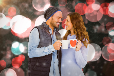 Young couple holding coffee mug against digitally generated twinkling light design