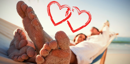 boy long hair: Close up of sandy feet of couple in a hammock against print Stock Photo
