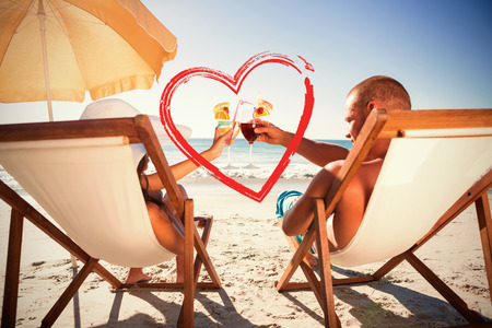 clinking: Happy couple clinking their glasses while relaxing on their deck chairs against print Stock Photo