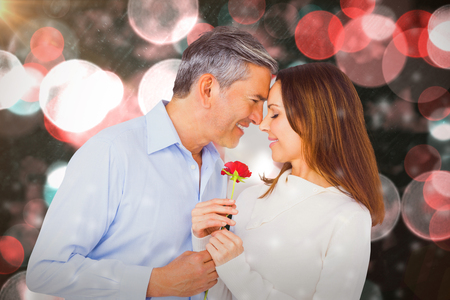 Happy couple holding flower against digitally generated twinkling light design