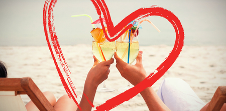 Couple clinking glasses of cocktail on beach against print Stock Photo