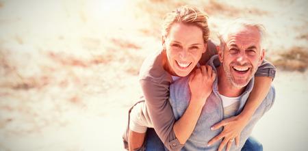 Porträt von den lachenden Paaren, die am Strand am sonnigen Tag stehen Standard-Bild - 71083591