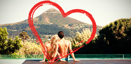 rear view of couple sitting by the pool Stock Photo