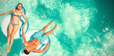 カップル スイミング プールで lilos でリラックス 写真素材