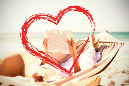 Woman reading book on hammock at beach against print