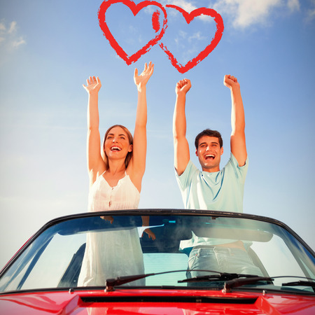 Cheerful couple standing in red cabriolet against print