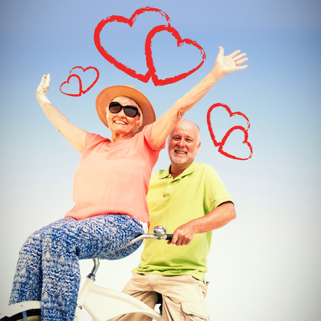 senior couple on bicycle against sky