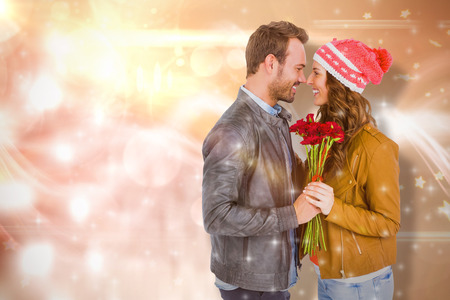 Young couple holding  flowers  against glowing background Stock Photo
