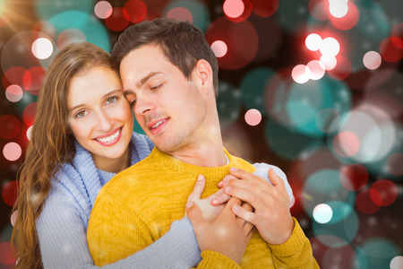 Smiling couple embracing  against digitally generated twinkling light design