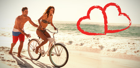 Print against couple riding bicycle at beach