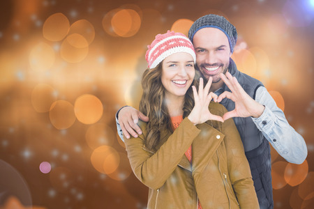 bobble: Happy young couple making heart shape with hands against glowing background Stock Photo