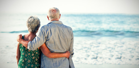 Vue arrière du couple de personnes âgées à la plage contre la mer Banque d'images