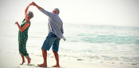 Coppia senior ballare in spiaggia sulla giornata di sole Archivio Fotografico - 71083791