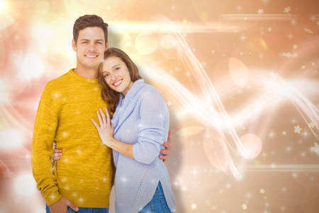 Portrait of smiling couple embracing against glowing background