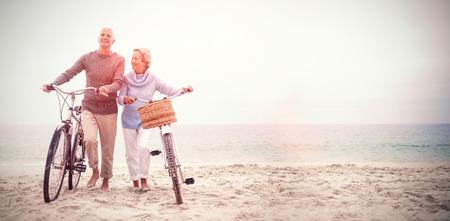 Toda la longitud de pareja de alto nivel con sus bicicletas en la playa Foto de archivo