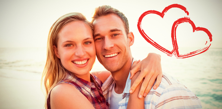 Couple embracing at beach against print Stock Photo