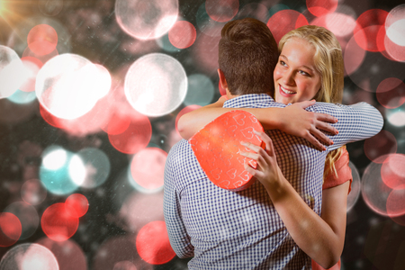 Couple embracing each other while holding gift against digitally generated twinkling light design Stock Photo