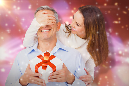 Wife covering eyes of husband  against glowing background