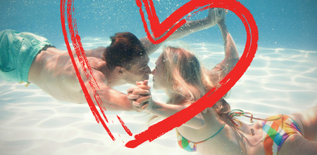 Cute couple kissing underwater in the swimming pool against print