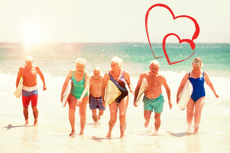 companionship: seniors holding surfboards at the beach