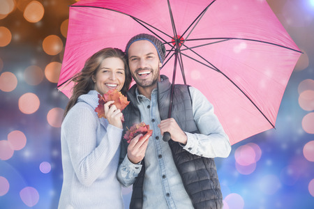 Happy young couple holding umbrella against glowing background