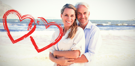 Happy couple hugging on the beach woman looking at camera against print Stock Photo