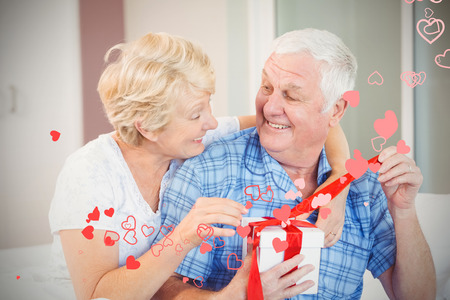 Valentines heart design against happy senior couple opening gift 3d Stock Photo