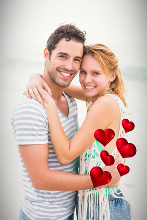 red hearts against portrait of young couple embracing at beach 3d Stock Photo