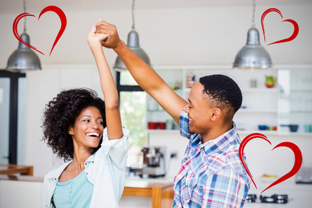 Heart against happy couple dancing in kitchen