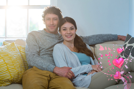 Valentines heart design against portrait of couple sitting on sofa 3d